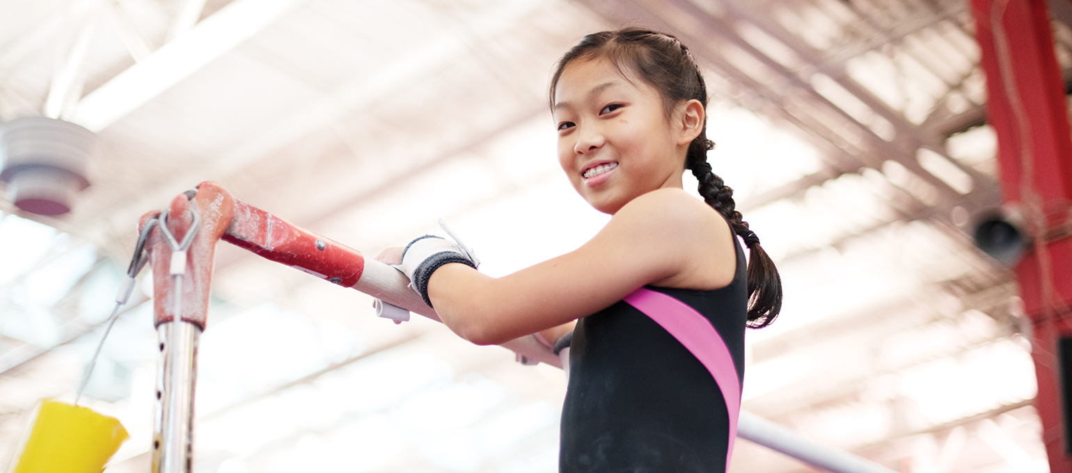Girl holding onto a pole and smiling toward the camera.