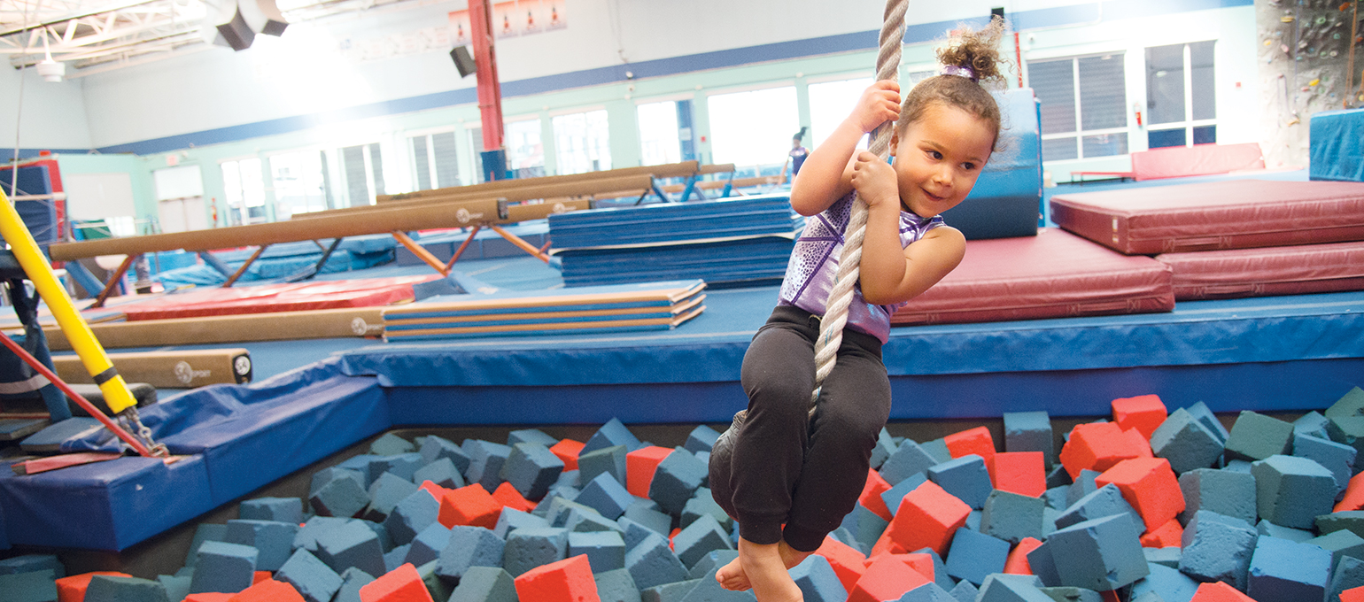 Child swinging on a rope over a foam block pit.