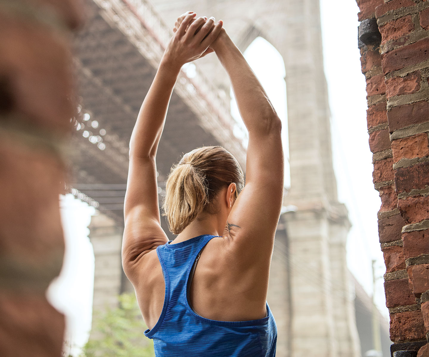 A woman stretching while working out in Brookyln Bridge Park.