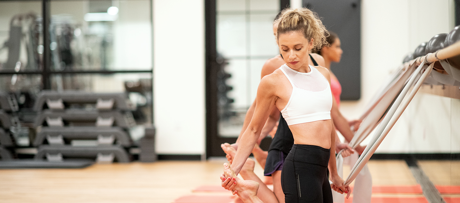 Women stretching in group Evolve Barre class at Chelsea Piers