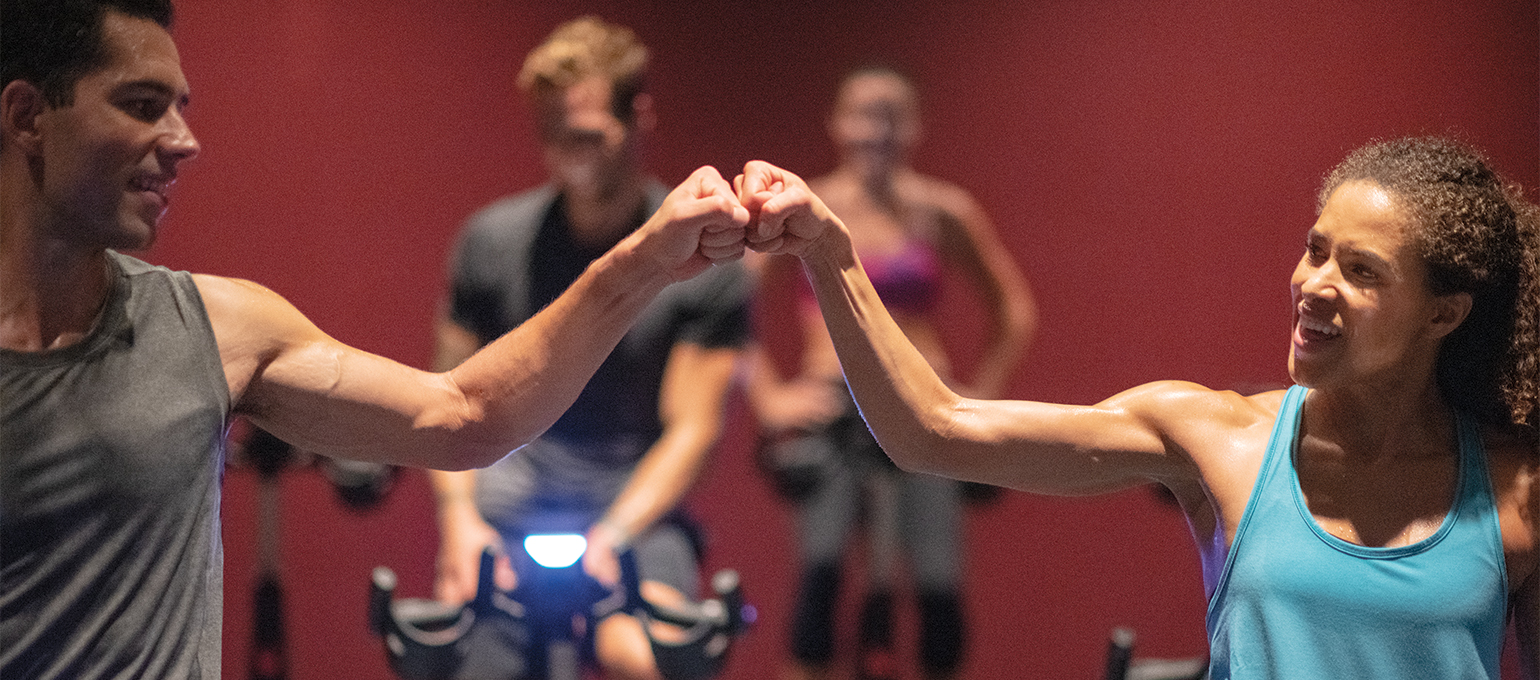 Two members share a fist bump after indoor cycling class