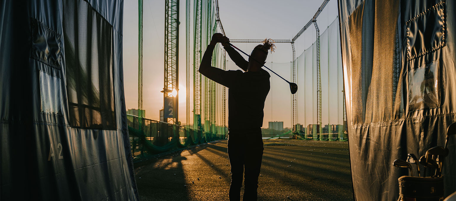 Golfer hitting a ball in the sunset